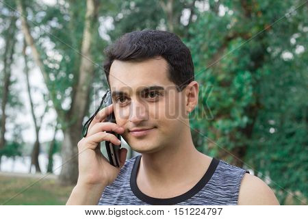 Young fitness man talks by mobile phone during training workout outdoor