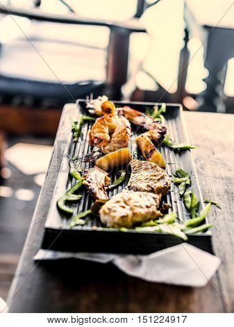 appetizing grilled seafood with green sweet pepper on black plate, top view