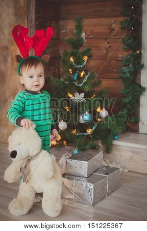 Funny boy with christmas deer horns stay near christmas tree. Christmas decoration. concept