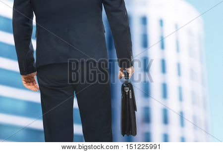 Businessman with briefcase in hand  on blurred building background. Lawyer and notary concept.