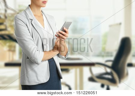 Businesswoman with phone on blurred office background. Lawyer and notary concept.