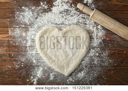 Pizza dough in heart shape with flour on table