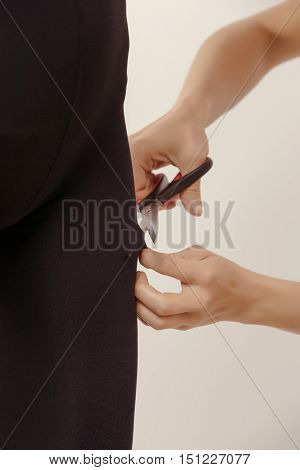 female hands scissor, cutting tights on beautiful woman legs in black nylon pantyhose