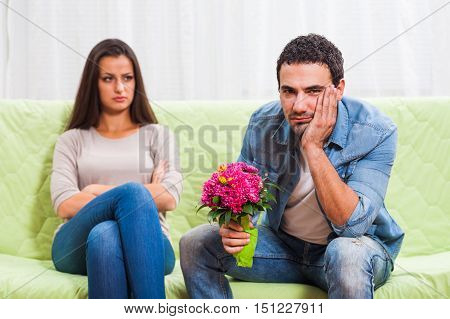 Young couple is sitting at sofa at home. Woman is angry.