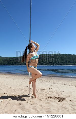girl in bathing suit with pole for dancing on summer river beach