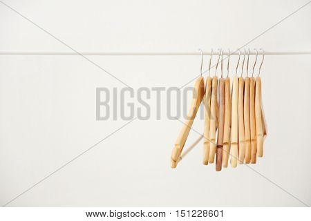 Wooden coat hangers on clothes rail and white background