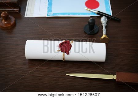Tied scroll with old notarial wax seal and stamp on table