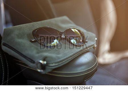 Female bag with sunglasses in car, closeup