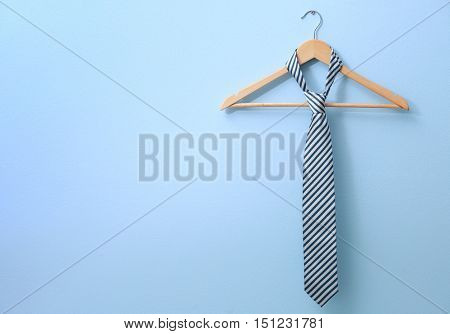 Male tie hanging on the rack, blue background