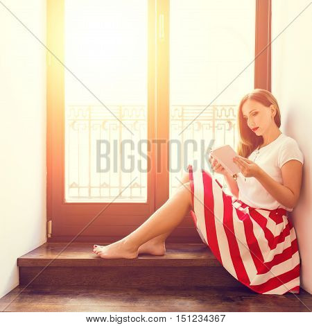 Young Stylish Lady Reading Book Near Balcony Door