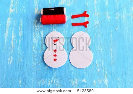 Christmas snowman ornament. Step. Cut from white felt details for sewing Christmas tree ornament. On one side embroidered with black thread eyes and mouth, red thread snowflakes and nose. Top view