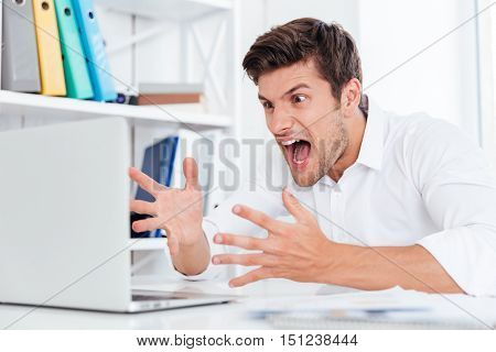Furious angry young businessman working with computer and shouting at the office