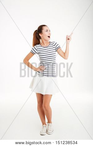 Cheerful excited young woman in skirt standing and pointing finger away over white background