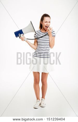 Full length portrait of a young woman shouting in megaphone with eyes closed isolated on a white background