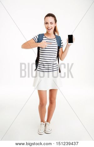 Young cheerful woman with backpack pointing finger at blank screen smartphone and winking isolated on a white background