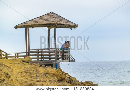 SALINAS, ECUADOR, OCTOBER - 2015 - Young couple watching the view at La chocolatera a famous nature viewpoint towars the pacific ocean located at rocky coast in Salinas Ecuador