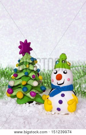 New Year tree and cheerful snowman from plasticine on a snow white background.