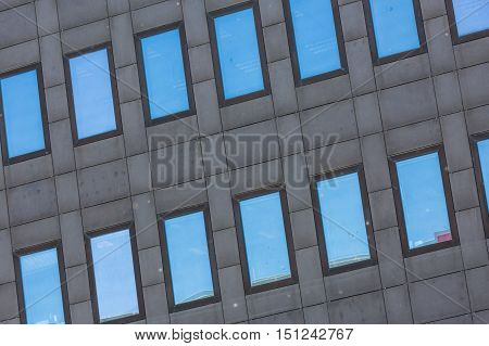 A Dark Grey Tall Building With Reflective Glass Windows