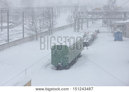 Snowfall in the city at the railway station with a green wagon and industrial buildings in the snowdrifts