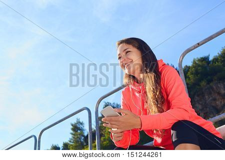 Woman Sitting With Phone On The Tribune Stadium .