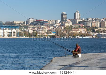 Fisherman sitting at Seafront Promenade urban Middle Eastern City scape on Background. Istanbul, Turkey, November 20, 2015