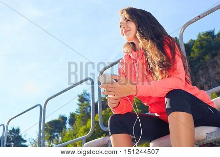Woman Listens To Music On Phone On The Tribune Stadium .