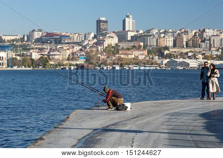 Fisherman sitting at Seafront Promenade and romantic Couple walking urban modern City scape on Background. Istanbul, Turkey, November 20, 2015