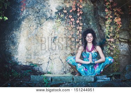 young woman in yoga meditation outdoor shot in front rock with autumn leaves