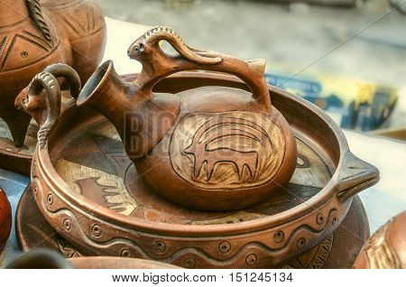 Souvenirs of clay wine jug on clay dish with relief pattern on Sunday clearance sale