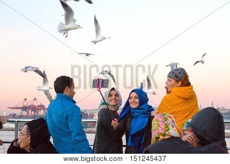 Excited People Passengers of Ferry Boat in Arabian and European clothing feeding Sea Gulls chasing Ship. Istanbul, Turkey, November 20, 2015