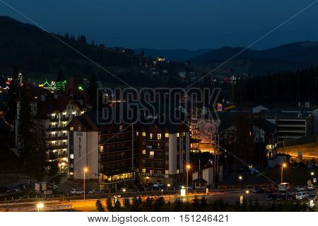 Bukovel Ukraine 04.08.2016. Bukovel resort town at night. Hotel complexes are illuminated street light. Cars are parked in the parking lot.