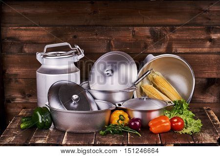 Differentcast aluminium pots, pans and watering can on old grunge wooden table against wood wall background