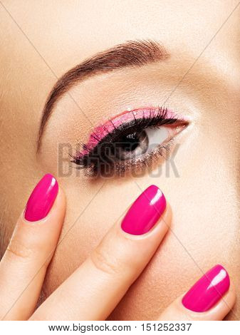 Closeup woman face with pink nails near eyes. Fingernails with pink manicure