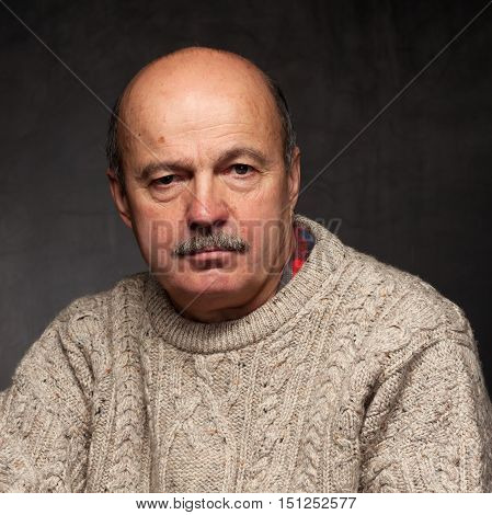 elderly man sits and looks thoughtfully pondering problem or complex issue in sweater.