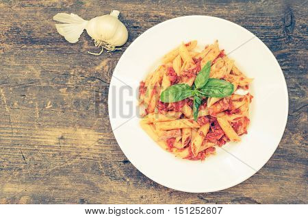 Italian Wholemeal Pasta Penne with Tuna and Basil. Fresh pasta with tuna and tomato sauce on old wooden background with place for text. Italian cuisine concept. Copy space. Top view.