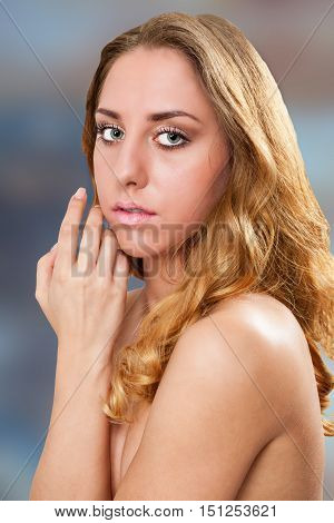 A gorgeous blonde woman touching her face