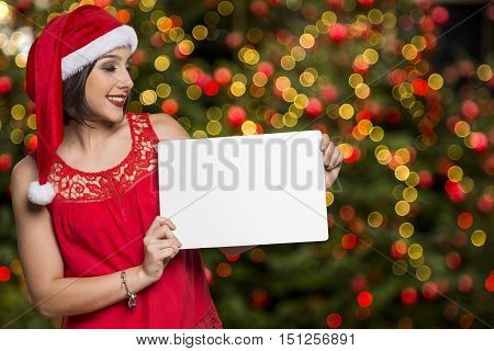 Holidays, Christmas. Portrait Of Smiling Woman Wearing Santa Hat Showing Whiteboard Banner Over Chri