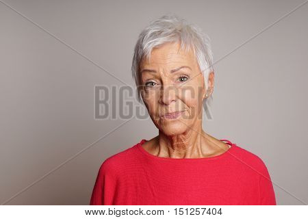mature woman in her sixties with a skeptical look on her face