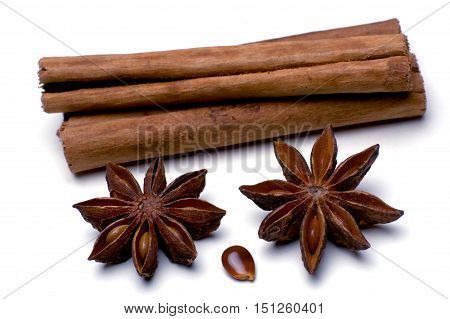 macro shot star anise and cinnamon sticks isolated in front of a white background