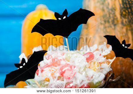 Halloween paper bats pumpkins and candy bucket on blue backround