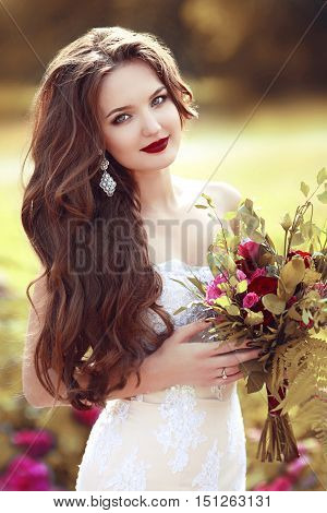 Wedding Portrait Of Beautiful Happy Bride With Long Wavy Hair Holding Bouquet Of Rose Flowers Posing