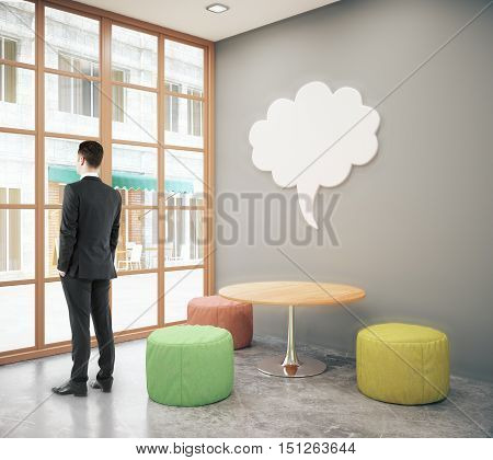 Businessman looking out of window in modern hipster interior with small coffee table seats and abstract thought cloud on wall. Mock up 3D Rendering