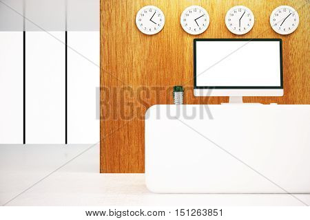 Front view of white reception desk with blank computer and several clocks on wooden wall. Mock up 3D Rendering