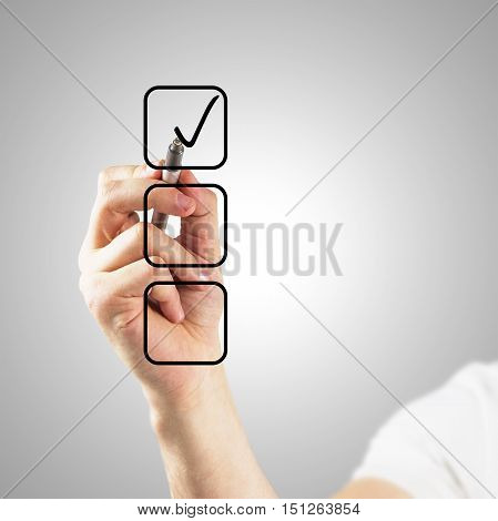 Close up of man's hand choosing one of three options by ticking a box on light grey background. Choice concept