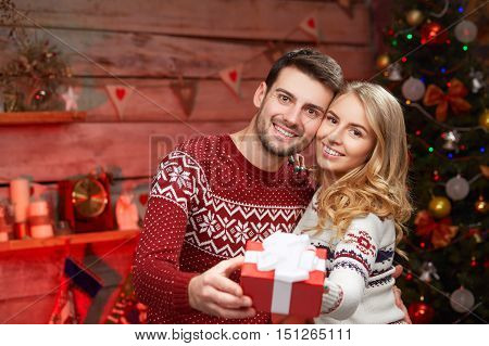romantic couple in a sweaters with gift box. Xmas concept. Handsome guy and beautiful blond girl hugging and holding a christmas present