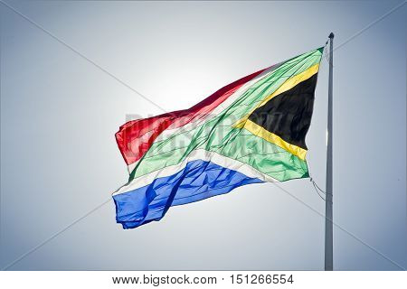 Large south african flag with the sun shining from behind
