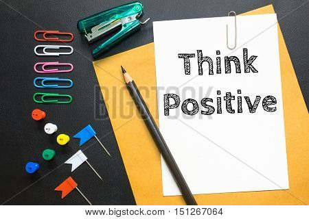 Text Think positive on white paper / business concept