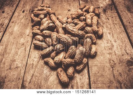 Close-up of peanuts in shell arranged in heart shape on wooden background. Natural food love
