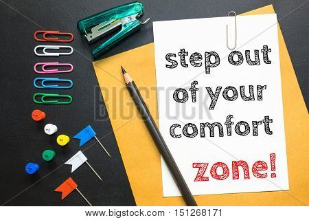 Text step out of your comfort zone on white paper / business concept