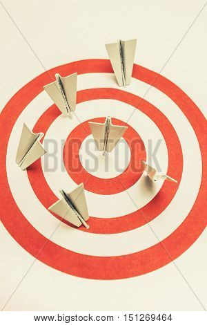 Corporate still-life photo on hits and misses on a target pin board scattered with aeroplane darts
